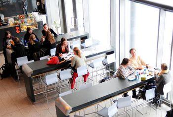 Mange studenter sitter ved flere bort i en kafffebar