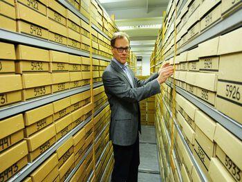 Ein mann viser fram ei samling med reolar med pappkassar som inneheld skjelett