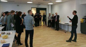 Ein mann står og snakkar medan han dirigerer med hendene medan fleire personar står i ring i møtelokalet.