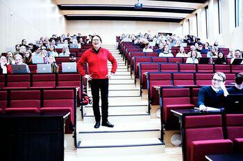 Dekan Raghild Hennum står i midtgangen i et stort auditorium, halvfullt med studenter