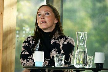 Ei kvinne sit ved eit bord der det er plassert vasskaraffel og glas og krus